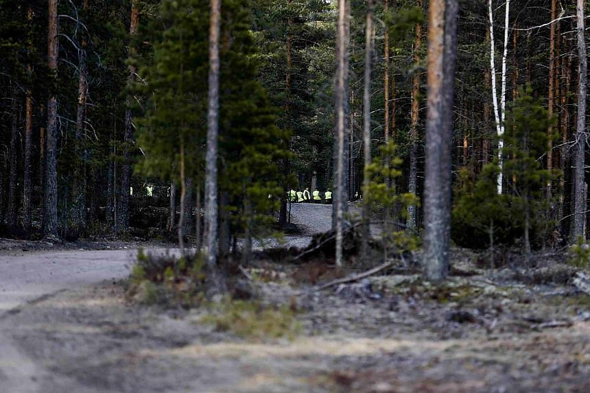 Personnel taking part in a search and rescue operation are seen in a forest near the Jamijarvi Airfield, southwest Finland, where a small passenger plane carrying parachuters crashed on April 20, 2014. -- PHOTO: REUTERS