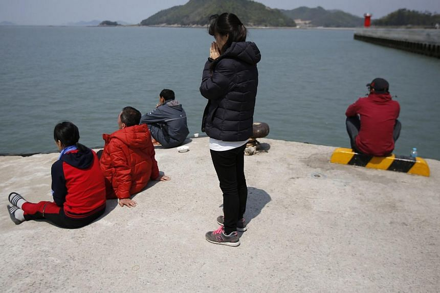 A family member of missing passengers (centre) who were on the South Korean passenger ferry Sewol prays toward the sea at a Jindo port where family members of missing passengers gathered on April 21, 2014. -- PHOTO: REUTERS
