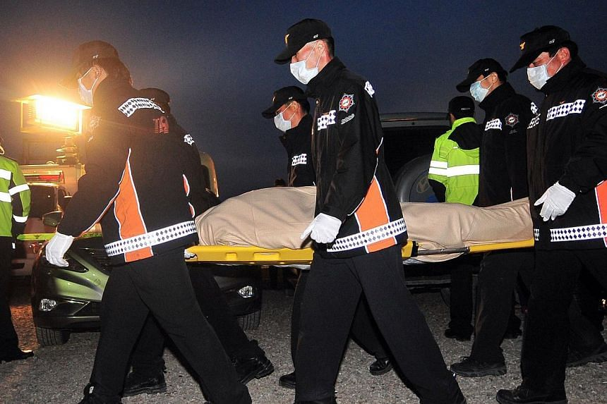 Members of a rescue team carry the body of a passenger retrieved from aboard the sunken South Korean ferry Sewol at a harbour in Jindo on April 20, 2014. -- PHOTO: AFP