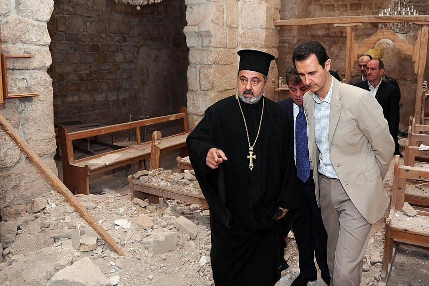 Syria's President Bashar al-Assad (in light coloured suit) looking at the damaged interior of a monastery in the ancient Christian town of Maalula which his troops recently recaptured from rebels on April 20, 2014. -- PHOTO: AFP/SANA