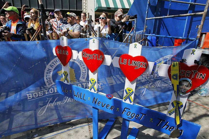 A handmade memorial to the victims of the 2013 Boston Marathon bombings stands at the site of the first bomb blast as the crowd marks the time that the bomb exploded one year ago, during the 118th running of the Boston Marathon in Boston. -- PHOTO: R