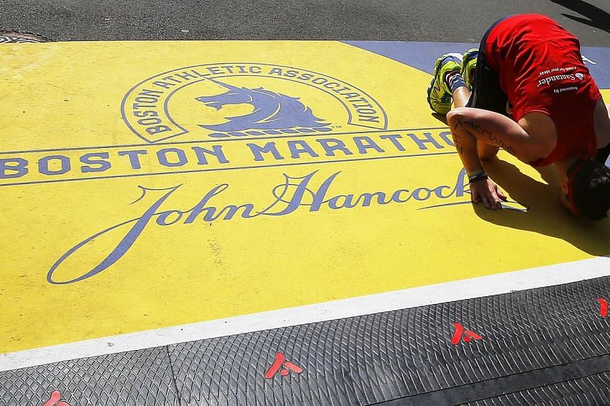 A runner kisses the finish line after completing the 118th Boston Marathon in Boston, Massachusetts April 21, 2014. Tens of thousands of runners, cheered by a multitude of spectators, streamed through the streets of Boston on Monday to reclaim t