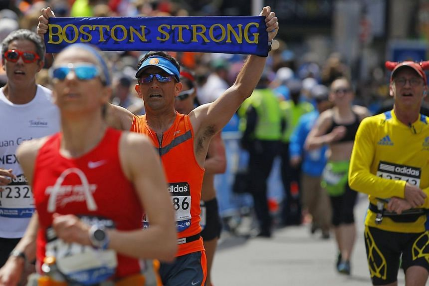 Martin Fierro carries a Boston Strong banner across the finish line during the 118th running of the Boston Marathon in Boston, Massachusetts on April 21, 2014. -- PHOTO: REUTERS