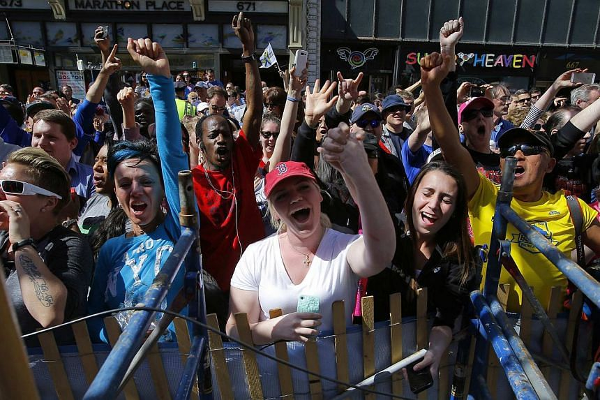 The crowd at the site of the first bomb blast cheers after a moment of silence for the victims of the 2013 Boston Marathon bombings during the 118th running of the Boston Marathon in Boston, Massachusetts on April 21, 2014. -- PHOTO: REUTERS