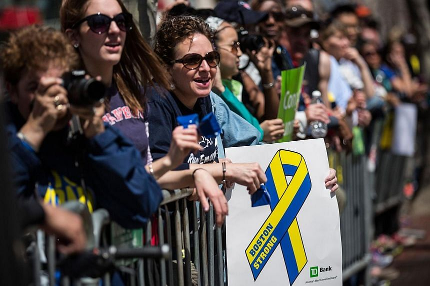 Fans with a Boston Strong poster cheer on runners as they finish the Boston Marathon on April 21, 2014 in Boston, Massachusetts. -- PHOTO: AFP