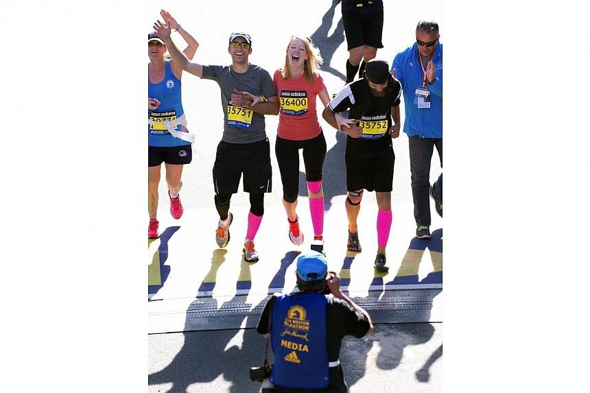 Boston Marathon bombing survivor Adrianne Haslet-Davis (Center) crosses the Boston Marathon finish line her twin older brothers Timothy (second from left) and David Haslet (second from right), in Boston, Massachusetts, April 21, 2014.Among the