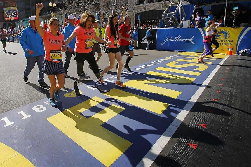 2013 Boston Marathon survivors Celeste (second from left) and Sydney Corcoran (centre) cross the finish line with Celeste's sister Carmen Acabbo, who ran the 118th Boston Marathon in Boston, Massachusetts April 21, 2014.Among the 36,000 runners