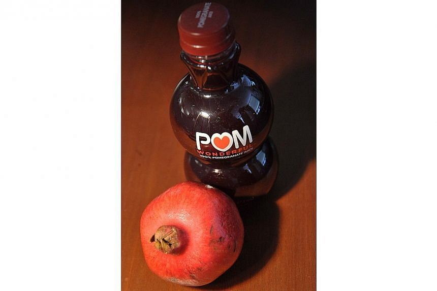 In this October 19, 2010 file photo illustration a bottle of POM Wonderful pomegranate juice is shown next to a pomegranate. The U.S. Supreme Court on April 21, 2014 heard an appeal by Pomegranate-juice maker POM Wonderful LLC, which alleges that Coc
