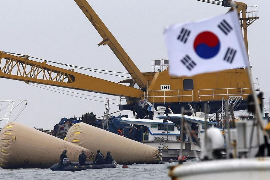 South Korean rescue workers operate near floats where capsized passenger ship Sewol sank on Wednesday, April 16, 2014, in the sea off Jindo on April 22, 2014.The confirmed death toll from South Korea's ferry disaster rose sharply to more than 1