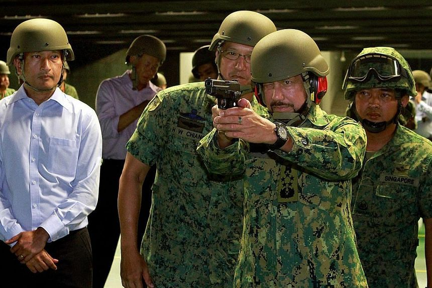 The Sultan of Brunei, Sultan Hassanal Bolkiah, (second, right) visited the Singapore Armed Forces' (SAF) Multi-Mission Range Complex at Pasir Laba on Tuesday and personally tried out some of its hardware. -- ST PHOTO:  LAU FOOK KO