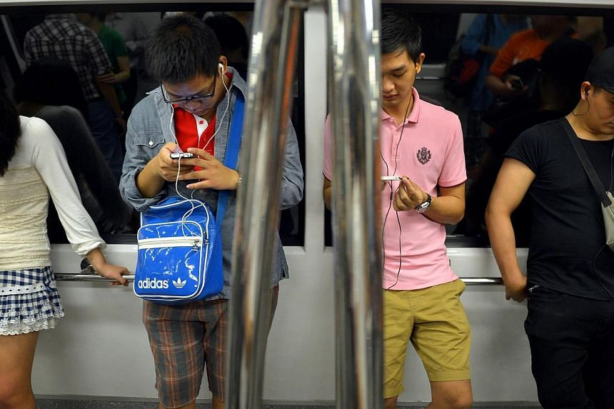 People using their mobile phones onboard a train travelling underground.Consumers here may soon have more choices as Singapore's telecommunications regulator is looking to ease in a fourth mobile operator here. -- ST FILE PHOTO:KUA CHEE S