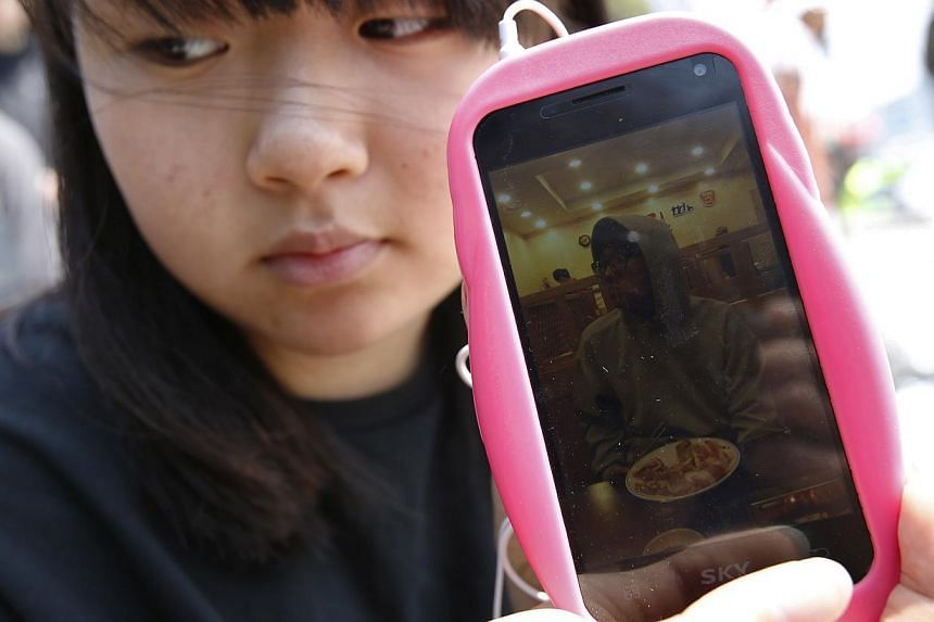 South Korean schoolgirl Cho A Reum shows a photo of her brother Cho Sung Won, one of the missing passengers onboard the South Korean ferry Sewol. The first alarm from the sinking ferry was raised in a phone call from a child on board to a fire statio
