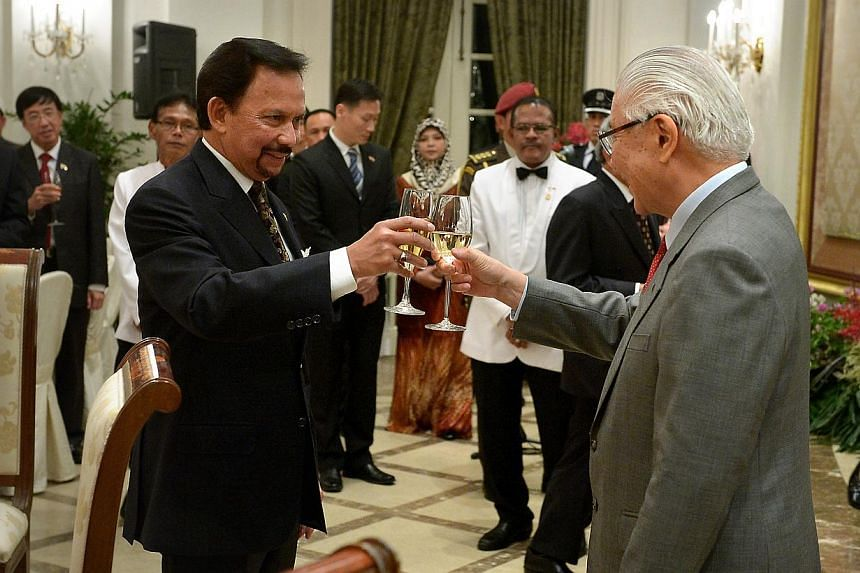 President Tony Tan Keng Yam and Brunei's Sultan Haji Hassanal Bolkiah toasting each other during a banquet at the Istana yesterday. -- ST PHOTO: KUA CHEE SIONG