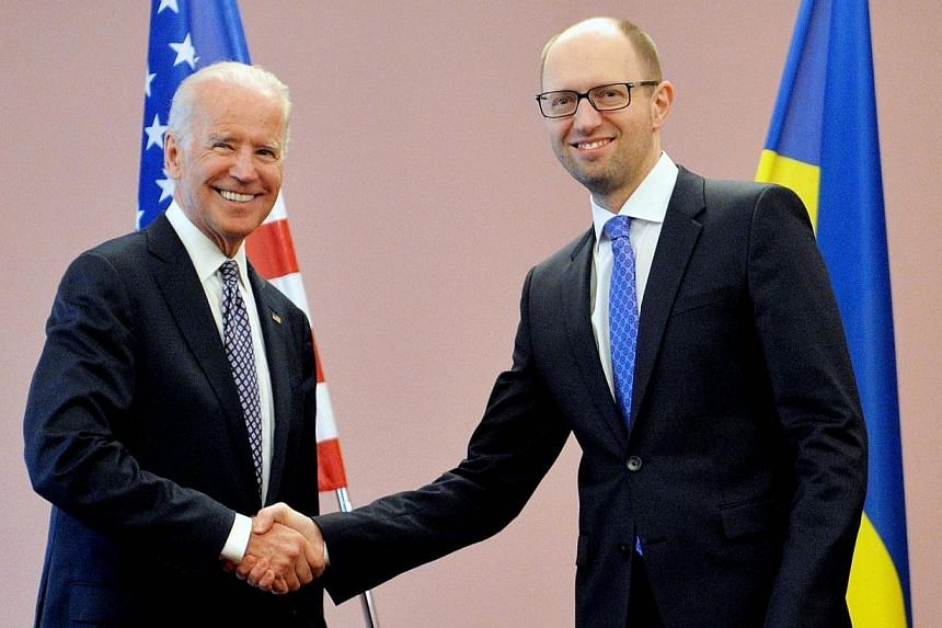 "Ukraine's acting Prime Minister Arseniy Yatsenyuk (right) shakes hands with US Vice President Joe Biden before their meeting in Kiev on April 22, 2014. US Vice President Joe Biden on Tuesday, April 22, 2014, accused Russia of ""trying to pul"