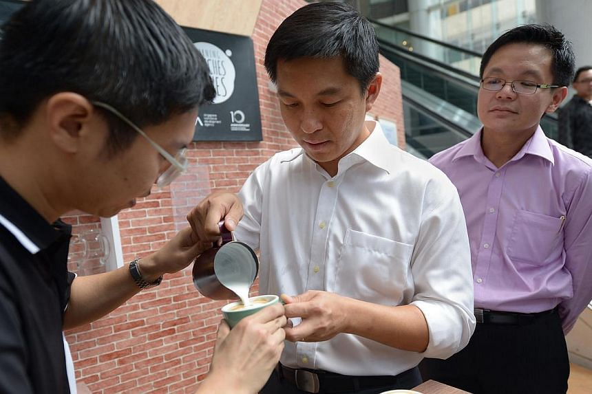 Coffee purveyor Ivan Kuek (left) helping Acting Minister for Manpower, Tan Chuan-jin (centre) in making coffee art at a roadshow organised for workers to learn more about training courses. He tried his hand at making coffee, re-learned his mothe