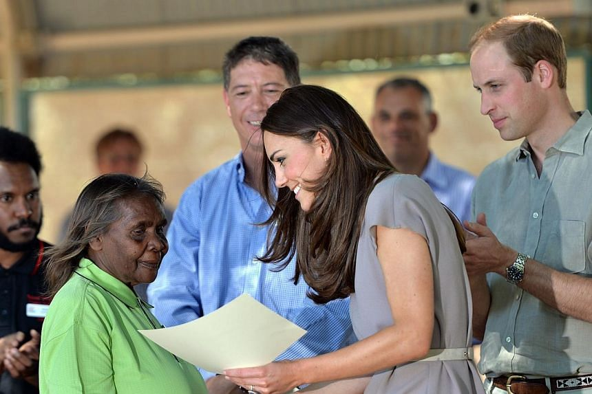 Catherine (second, right), the Duchess of Cambridge, distributes certificates to the graduating students at the National Indigenous Training Academy as her husband Prince William of Britain (right) looks on, in Uluru on April 22, 2014. -- PHOTO: AFP