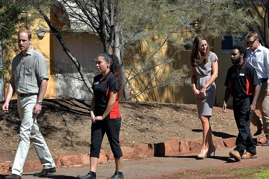 Britain's Prince William (left) and his wife Catherine (third, right), the Duchess of Cambridge, arrive to distribute certificates to the graduating students at the National Indigenous Training Academy in Uluru on April 22, 2014.-- PHOTO: AFP