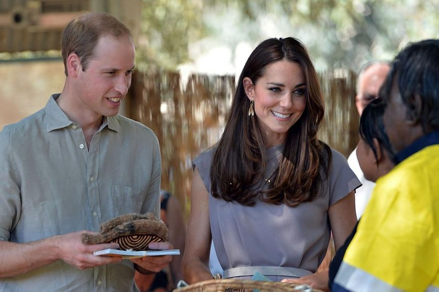 Britain's Prince William's (left) and his wife Catherine (centre) receives souvenir from Aboriginal students after distributiing certificates to graduating students at the National Indigenous Training Academy in Uluru on April 22, 2014.-- PHOTO