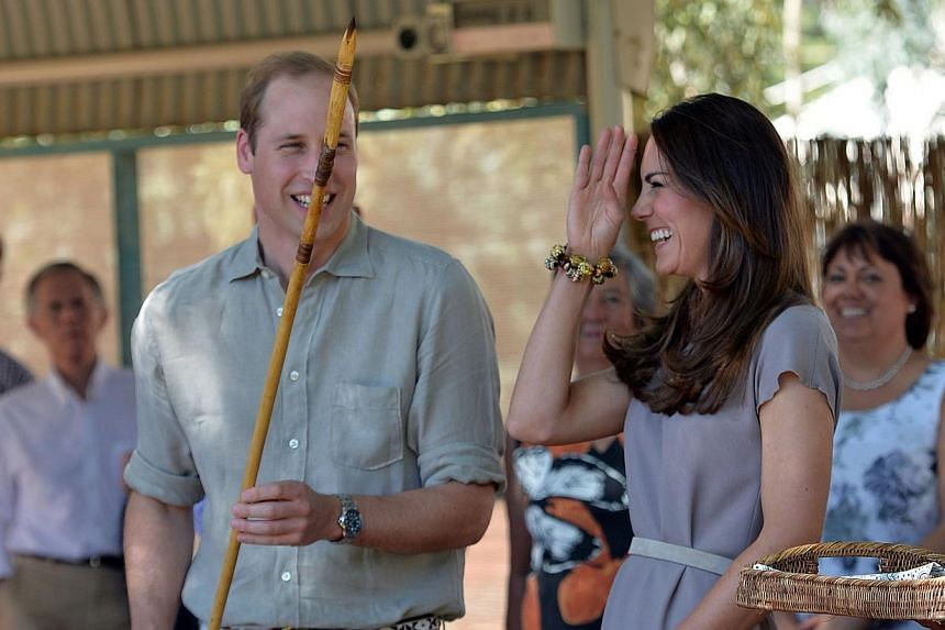 Britain's Prince William (right) and his wife Catherine share light moments after receiving a souvenir of a hunting spear from aboriginals during their visit to a training center in Uluru on April 22, 2014.-- PHOTO: AFP