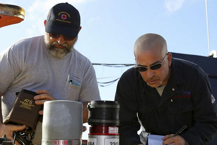 Charlie Kapica (left) and Chris Minor from Phoenix International conduct pre-deployment checks of the Artemis Autonomous Underwater Vehicle before beginning the search for the missing Malaysia Airlines Flight MH370 on April 20, 2014. A tropical