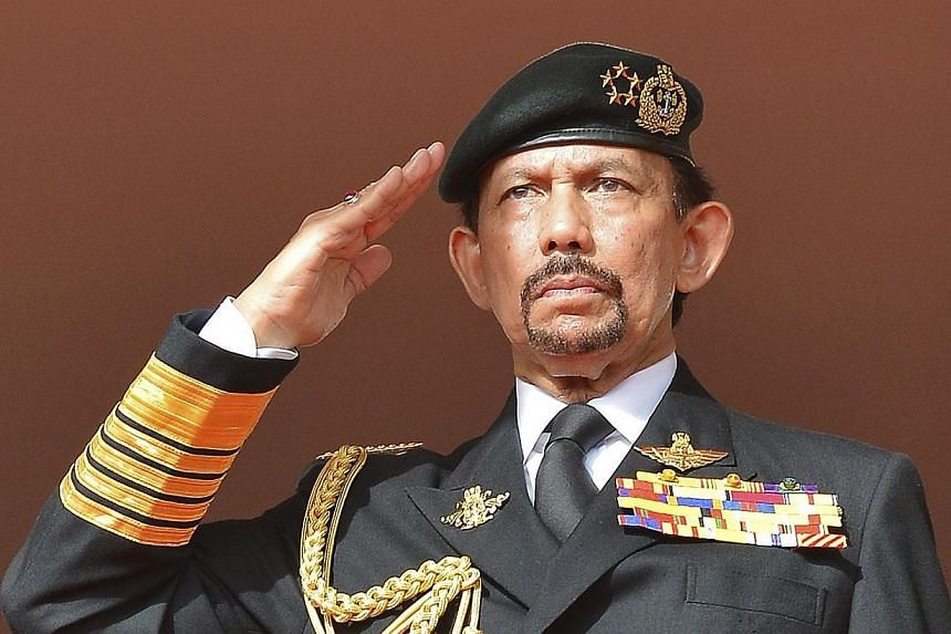 Brunei's Sultan Hassanal Bolkiah salutes as the national anthem is played during celebrations for Brunei's 30th National Day, in Bandar Seri Begawan on Feb 23, 2014.Brunei has postponed its implementation of harsh Islamic punishments, due to be