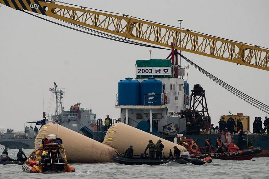 South Korean coast guards and rescue workers are seen at the accident site of the capsized South Korean ferry Sewol in Jindo on Tuesday, April 22, 2014.Crew members detained over South Korea's ferry disaster said on Tuesday they had done their