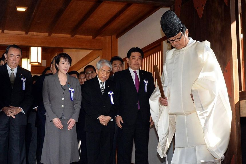 Japanese lawmakers following a Shinto priest (right) during a visit to the controversial Yasukuni shrine in Tokyo on April 22, 2014. -- PHOTO: AFP