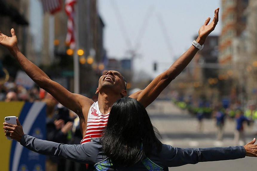 Meb Keflezighi of the US celebrates with his wife Yordanos Asgedom after winning the men's division at the 118th running of the Boston Marathon in Boston, Massachusetts, on April 21, 2014. - REUTERS/Brian Snyder