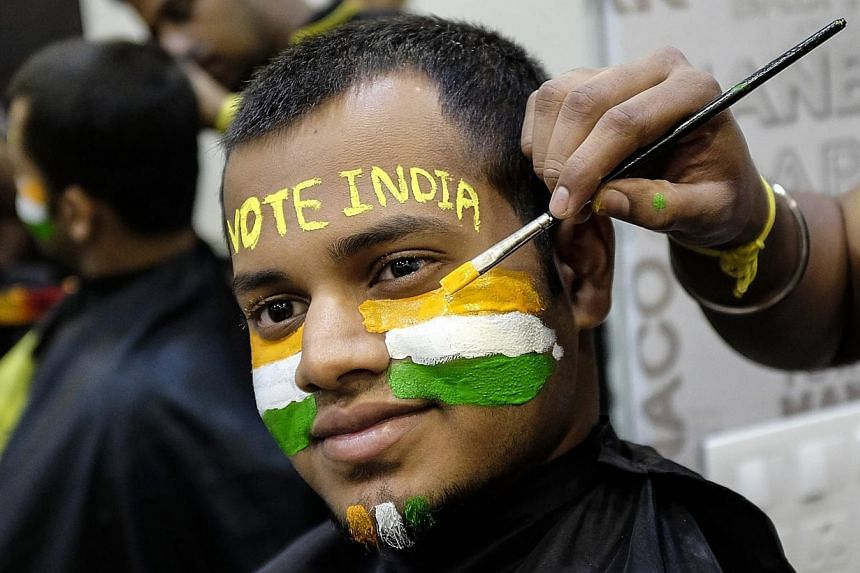 A man poses as he gets his face painted ahead of the sixth phase of India's general election in Mumbai April 23, 2014. Goats, cable television, blenders, fans, bicycles and gold are among freebies promised by regional parties as they campaign for nat