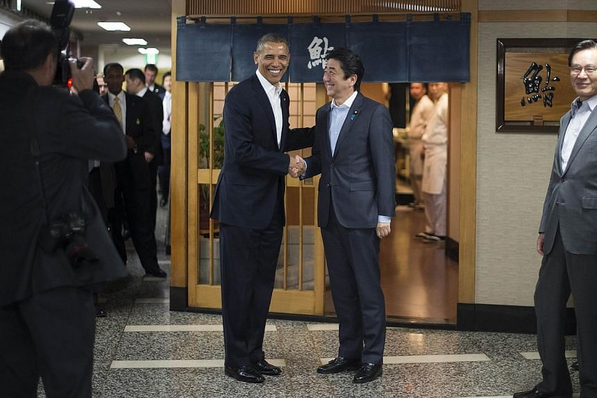 US President Barack Obama with Japanese Prime Minister Shinzo Abe before a private dinner at Sukiyabashi Jiro restaurant in Tokyo on April 23, 2014.Mr Obama dined on Wednesday at the tiny Tokyo sushi restaurant ruled with an iron rod by its red