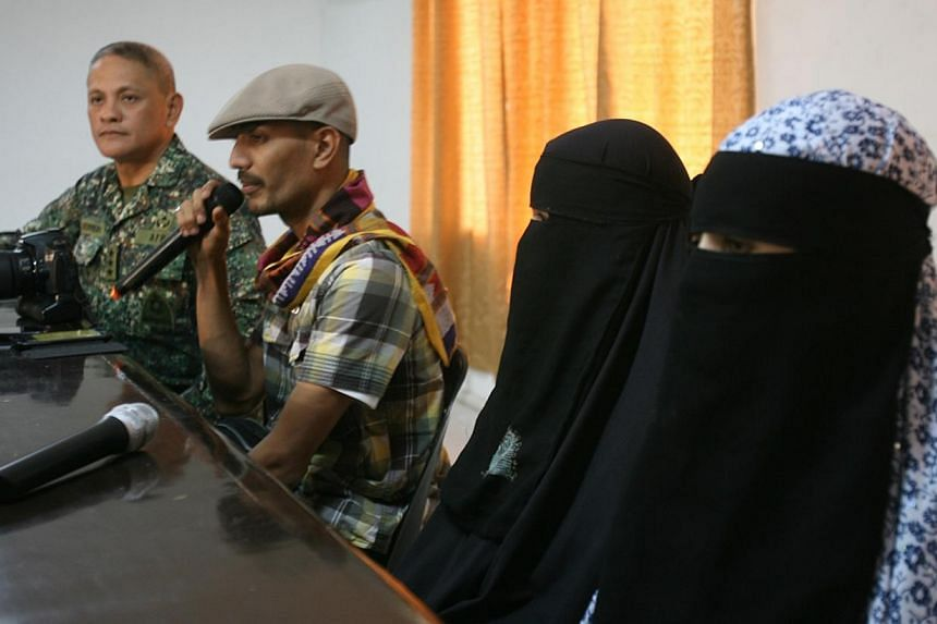 Freed captive Filipino-Algerian sisters Nadjoua and Linda Bansil clad in masturah and nijab veils are presented by their brother Mohammed Bansil (Second from Left) with military chief, Lieutenant General Rustico Guerrero (Left) during a briefing in a