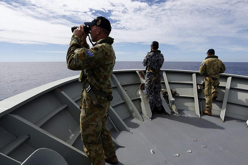 Gunner Richard Brown (left) of Transit Security Element looks through binoculars as he stands on lookout with other crew members aboard the Australian Navy ship HMAS Perth as they continue to search for missing Malaysian Airlines flight MH370 in this