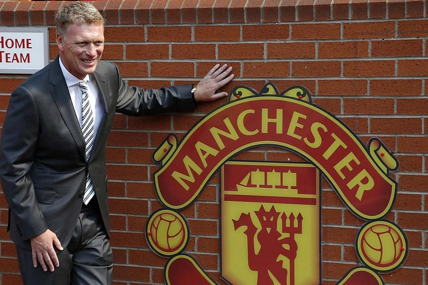 Then Manchester United manager David Moyes poses in front of the home team dugout before a news conference at Old trafford in Manchester, northern England in this July 5, 2013 file photo.Shares of Manchester United jumped 6 per cent on Tuesday