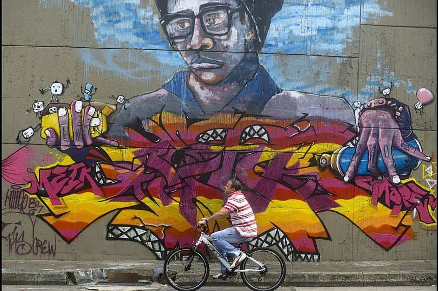 """A man rides his bicycle during the Day Without Cars under the slogan """"Turn off the engine, turn on your heart"""", (in Spanish ìApaga el motor, enciende tu corazonî), in Medellin, Antioquia department, Colombia on April 22, 2014. A municip"""