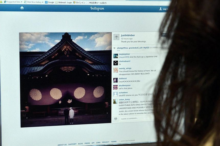 This photo illustration shows a woman looking at a picture of Japanese Yasukuni shrine posted on the Instagram account of Canadian pop singer Justin Bieber after his visit to the controversial shrine in Tokyo, on April 23, 2014. Justin Bieber courted