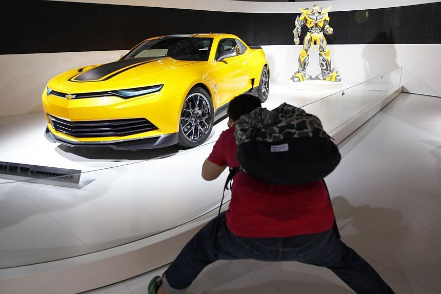 A visitor takes a photo of a Chevrolet Camaro car at the China International Exhibition Centre new venue during the Auto China 2014 Beijing International Automotive Exhibition in Beijing, on April 21, 2014. -- FILE PHOTO: AFP