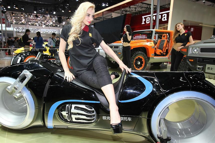 A model poses on a G. Patton electric motorbike on display at the China International Exhibition Centre during the Auto China 2014 Beijing International Automotive Exhibition in Beijing, on April 20, 2014. -- FILE PHOTO: AFP