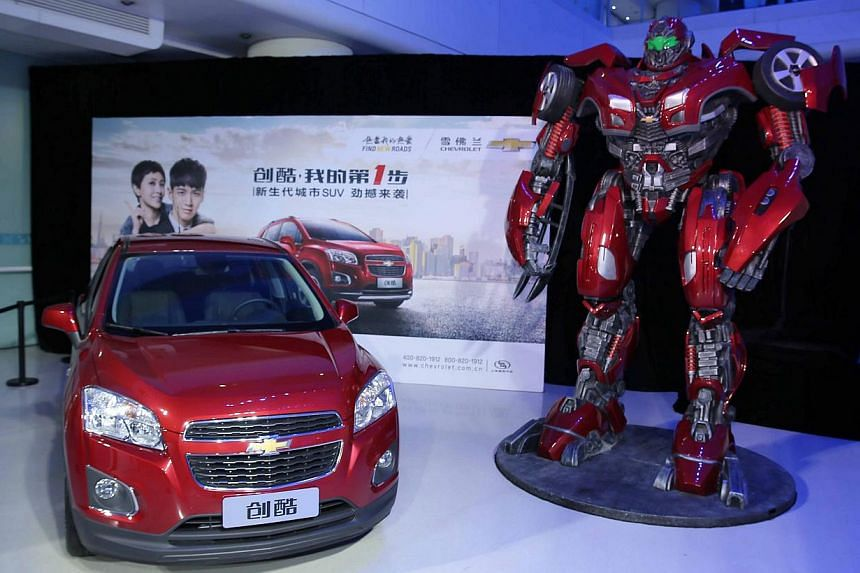 Dancers performing around a new Chevrolet Trax car during the Chevrolet Gala Night of the General Motors (GM), ahead of the Auto China 2014 Beijing International Automotive Exhibition in Beijing, on April 19, 2014. -- FILE PHOTO: AFP
