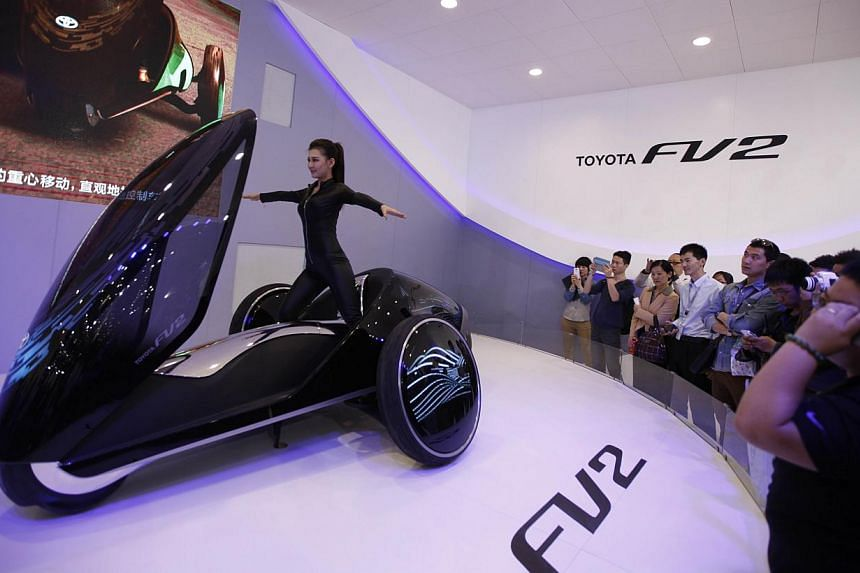 A model (centre) poses on a Toyota FV2 concept car at the China International Exhibition Centre new venue during the Auto China 2014 Beijing International Automotive Exhibition in Beijing, on April 21, 2014. -- FILE PHOTO: AFP