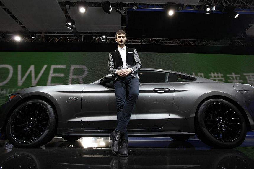 A model poses by a Mustang 50th anniversary edition car on display at the China International Exhibition Centre new venue during the Auto China 2014 Beijing International Automotive Exhibition in Beijing, on April 21, 2014. -- FILE PHOTO: AFP