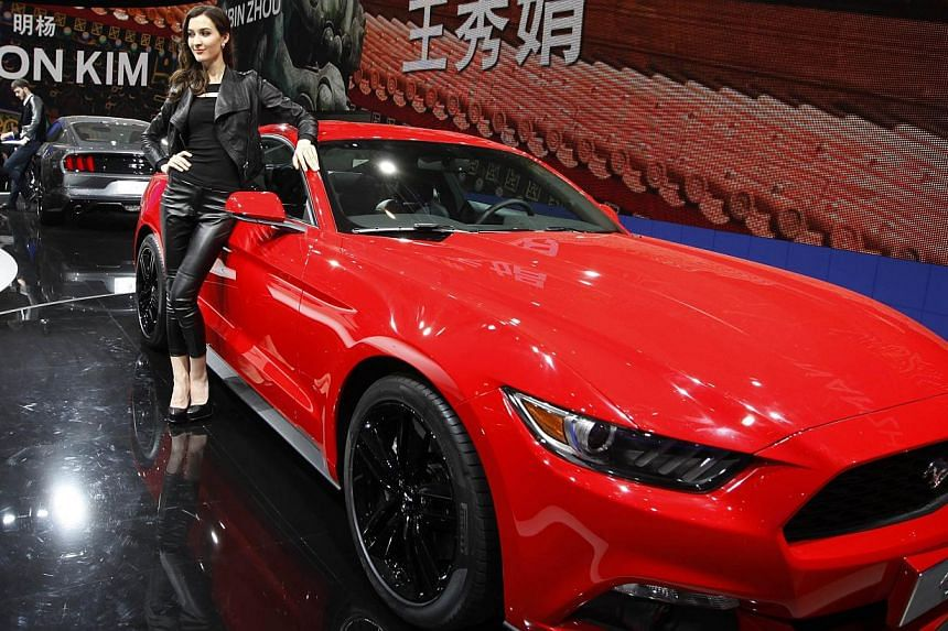 A model poses by a red Mustang 50th anniversary edition car on display at the China International Exhibition Centre new venue during the Auto China 2014 Beijing International Automotive Exhibition in Beijing, on April 21, 2014. -- FILE PHOTO: AFP