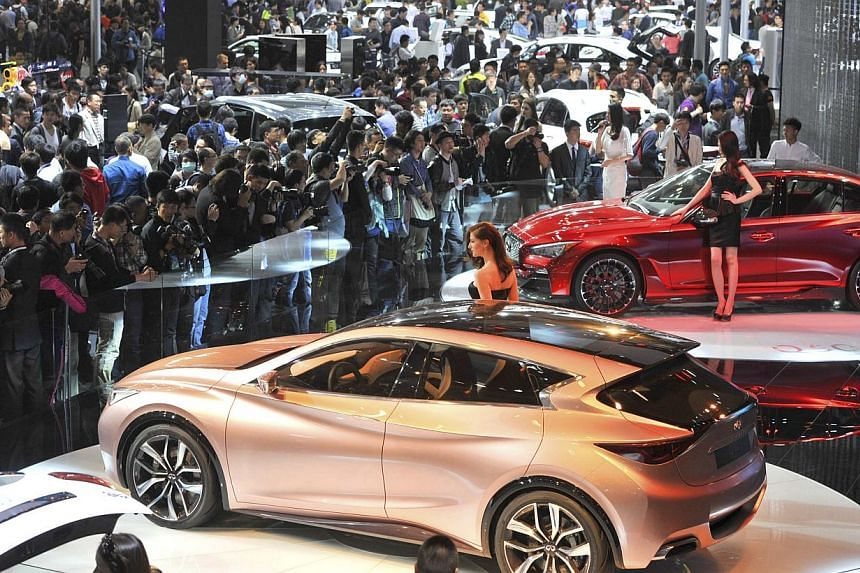 Visitors crowd in front of the Infiniti exhibition booth on the first public day of Auto China 2014 in Beijing, on April 21, 2014. -- FILE PHOTO: AFP