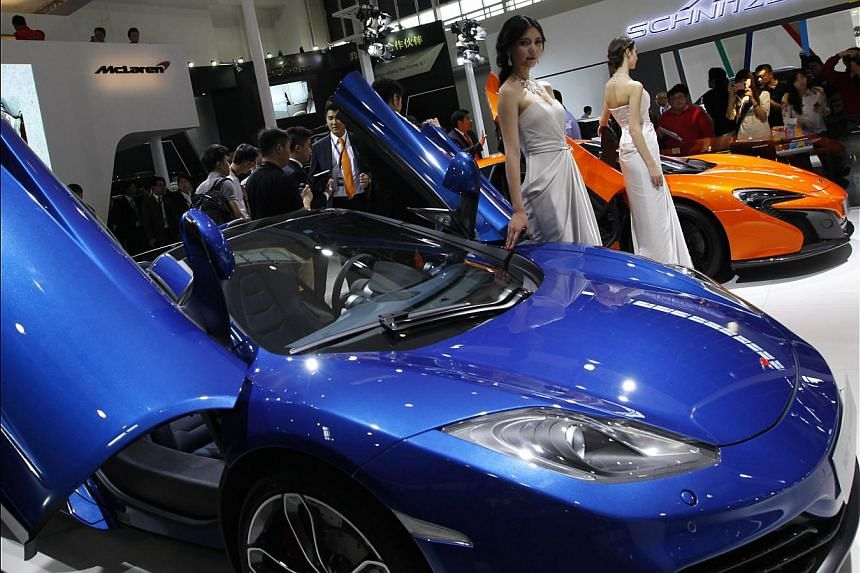 Models pose by McLaren cars on display at the China International Exhibition Centre new venue during the Auto China 2014 Beijing International Automotive Exhibition in Beijing, on April 21, 2014. -- FILE PHOTO: AFP