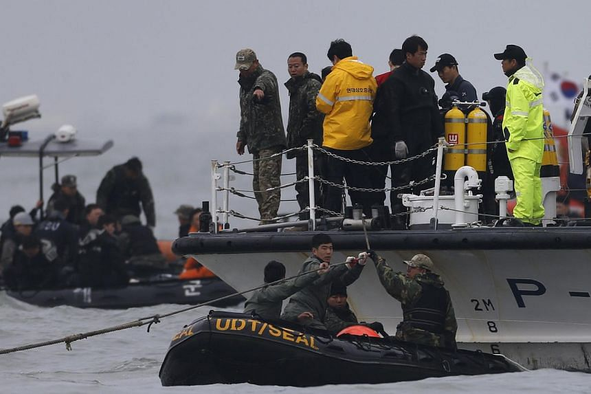 "Rescue workers operate near floats where the capsized passenger ship ""Sewol"" sank, during the rescue operation in the sea off Jindo, on April 19, 2014. The desperate, tragically fruitless search for survivors of South Korea's ferry disaster has so fa"