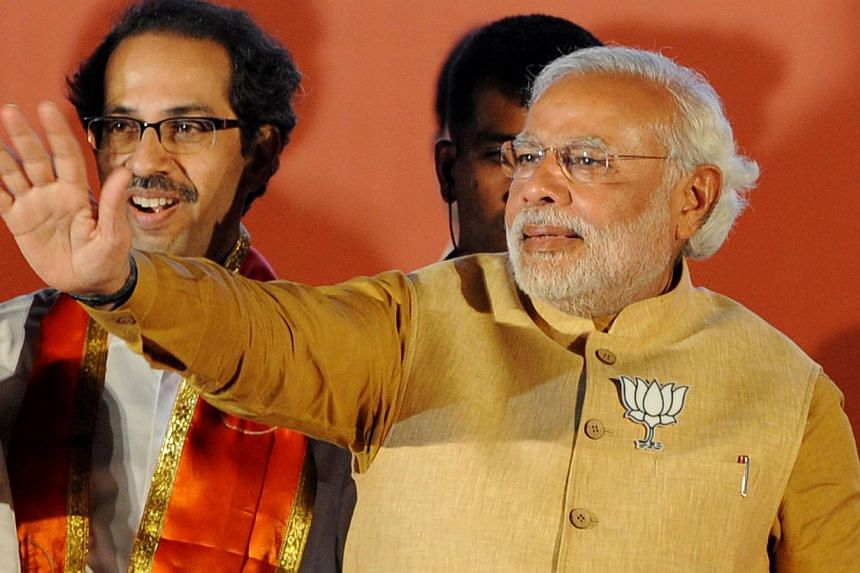 Chief Minister of the Indian state of Gujarat and Bharatiya Janata Party (BJP) prime ministerial candidate Narendra Modi (right) waves to supporters as Shiv Sena party chief Uddhav Thackeray looks on at an election rally in Mumbai, on April 21, 2014.
