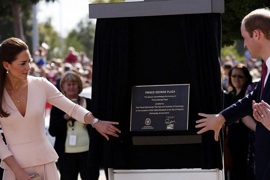 Britain's Prince William (right) and his wife Catherine, the Duchess of Cambridge, unveil a plaque naming a plaza after their son Prince George outside the Playford Civic Centre in the Adelaide suburb of Elizabeth, on April 23, 2014. -- PHOTO: REUTER