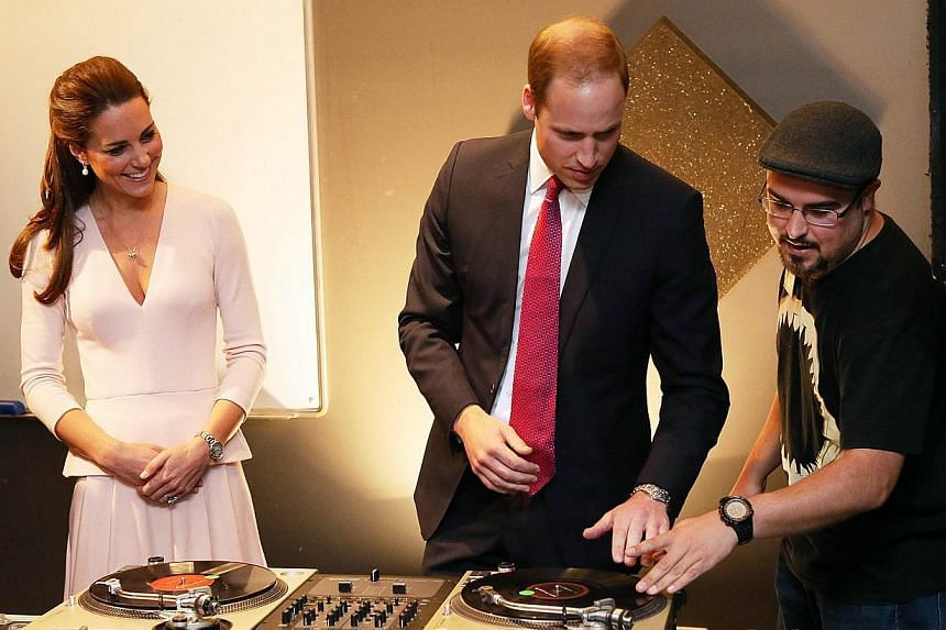 Catherine, Duchess of Cambridge (left) looks on as Prince William, Duke of Cambridge (second, left) is shown how to play on DJ decks at the youth community centre, The Northern Sound System in Elizabeth near Adelaide, on April 23, 2014. Prince Willia