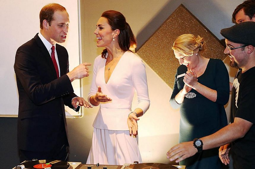Catherine, Duchess of Cambridge (second, left) gestures to Prince William, Duke of Cambridge (left) to play on DJ decks at the Northern Sound System in Elizabeth near Adelaide, on April 23, 2014. -- PHOTO: REUTERS