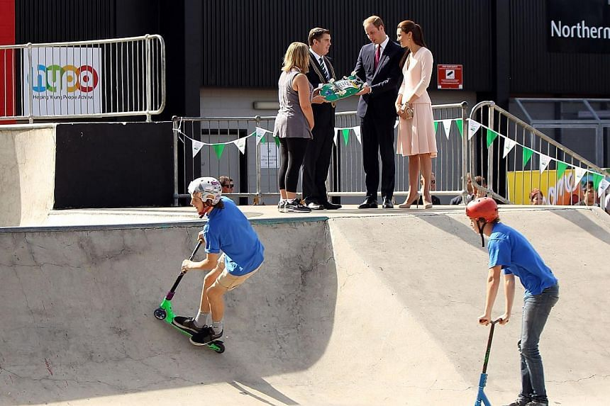 City of Playford Mayor Glenn Docherty (top second from left) presents a skateboard to Britain's Prince William (top second from right) and his wife Catherine, the Duchess of Cambridge (top right), during a visit to a skate park in Elizabeth, a suburb