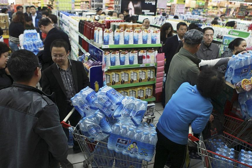 People line up to buy cartons of bottled water at a supermarket after reports on heavy levels of benzene in local tap water, in Lanzhou, Gansu province, on April 11, 2014. Sixty per cent of underground water in China which is officially monitored is